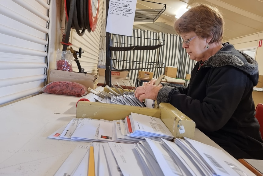 Woman in black jacket sitting down at a desk sorting piles of envelopes.
