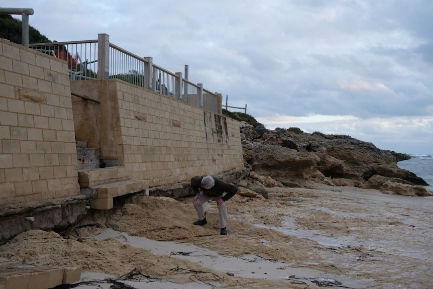A man looks at the underside of a beachfront wall