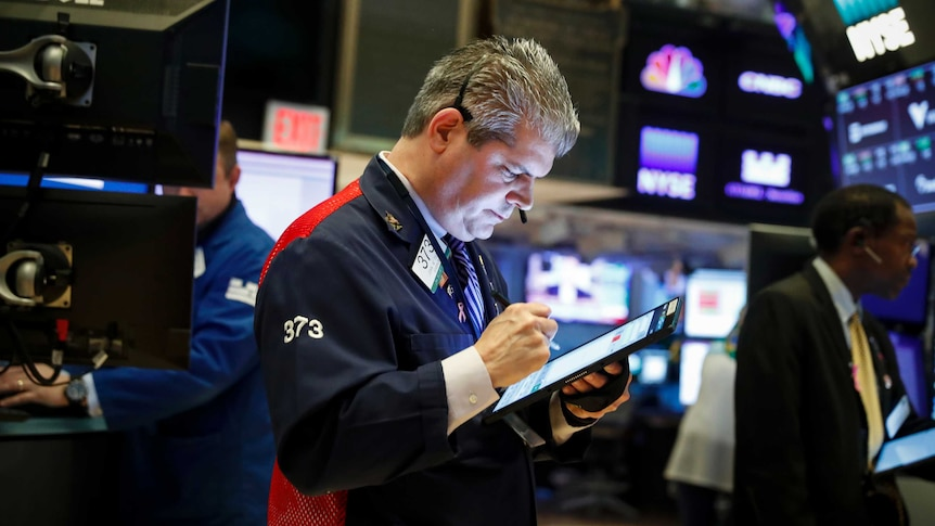 A stock trader looks down at a tablet as he works on the floor of a busy stock exchange while surrounded by screens.