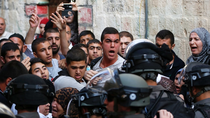 Palestinians shout in front of Israeli security forces who block a road leading to the Al-Aqsa mosque compound in Jerusalem's Old City