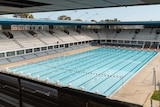 A picture of a still Olympic sized swimming pool taken from a grandstand