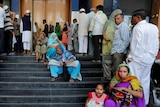 People queue outside a bank in India.