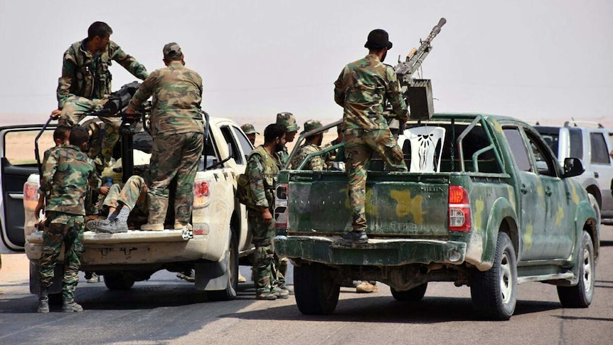 Armed soldiers ride in the back of utes in Deir Ezzor, Syria.