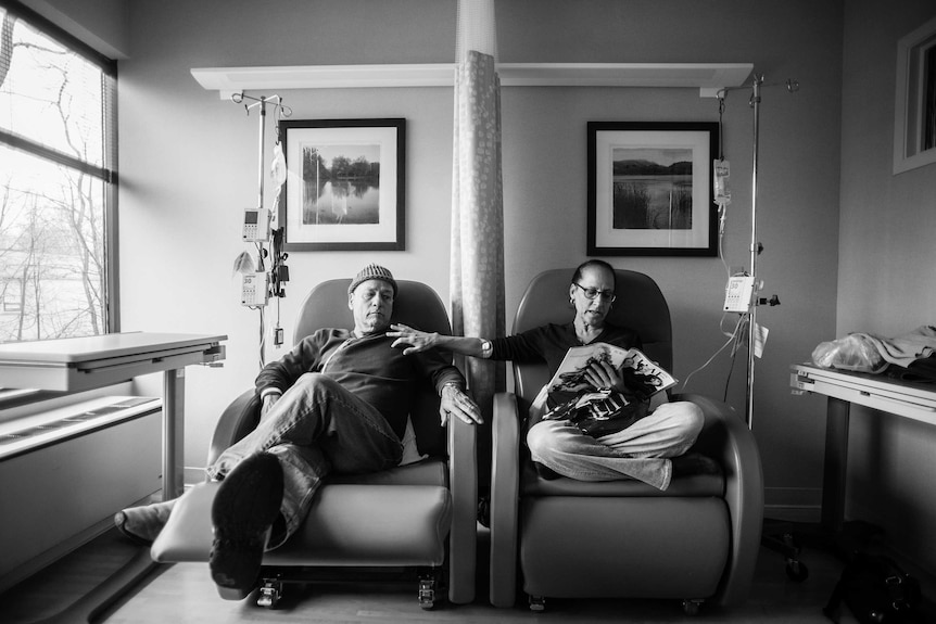 A man sits beside his wife as they get their weekly chemotherapy treatments.
