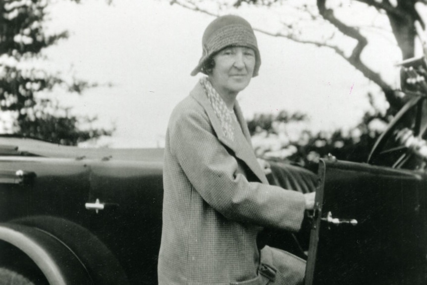 A black and white photo of older woman with a long jacket gets into a old-style car while looking at the camera.