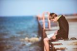 A boy sitting on a jetty reading.