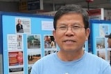 A man of Vietnamese heritage with black hair and glasses stands with his hands clasped in front of of him wearing a blue t-shirt