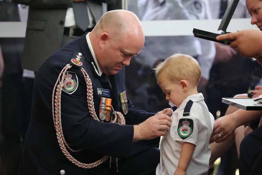 man pinning medal on toddler