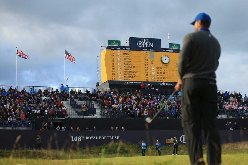 A golfer stands with his back to camera, looking at the green, with the leaderboard in front of him.