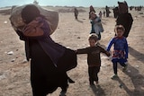A woman carries a laden sack on her right shoulder as she is trailed by two children who are holding hands