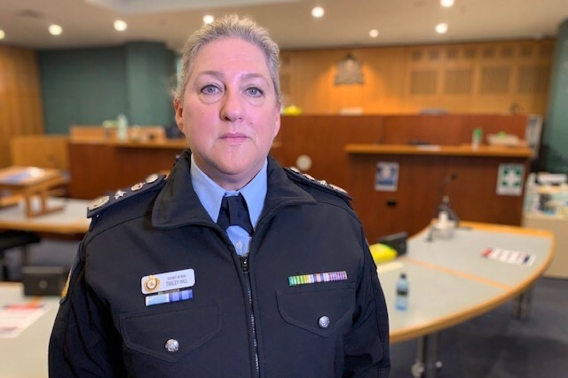 A woman in a uniform stands inside a courtroom.