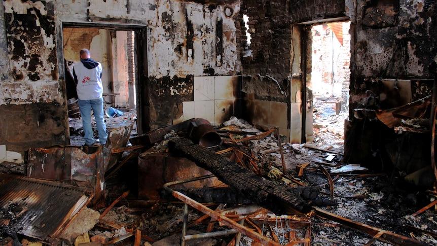 Staff members walk through the damaged MSF hospital.