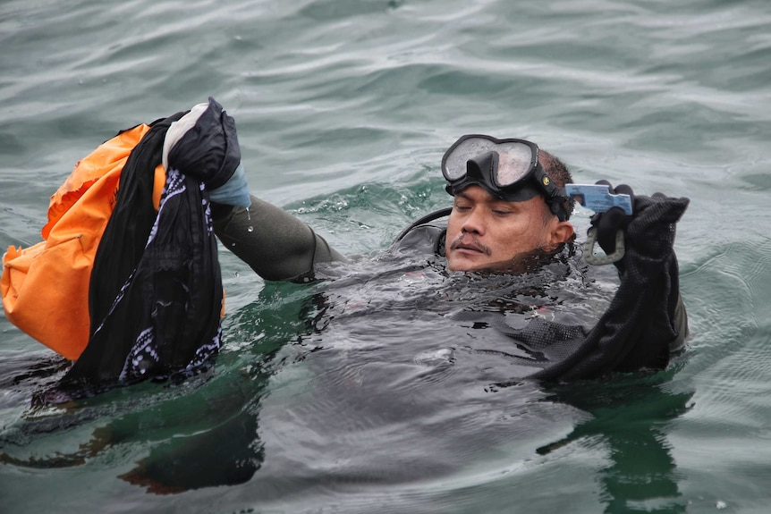 An Indonesian Navy diver shows debris recovered from the water