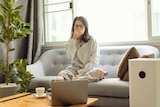 Woman on couch holding her nose looking at an air purifier