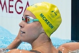 An Australian female swimmer looks back at the scoreboard after finishing a heat at the Tokyo Olympics.