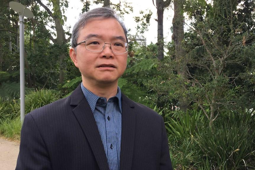 一名中年亚裔男子穿着西装在公园里讲话。