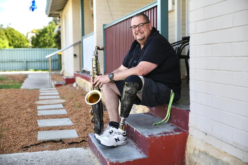 Andrew Fairbairn sitting on step playing sax.