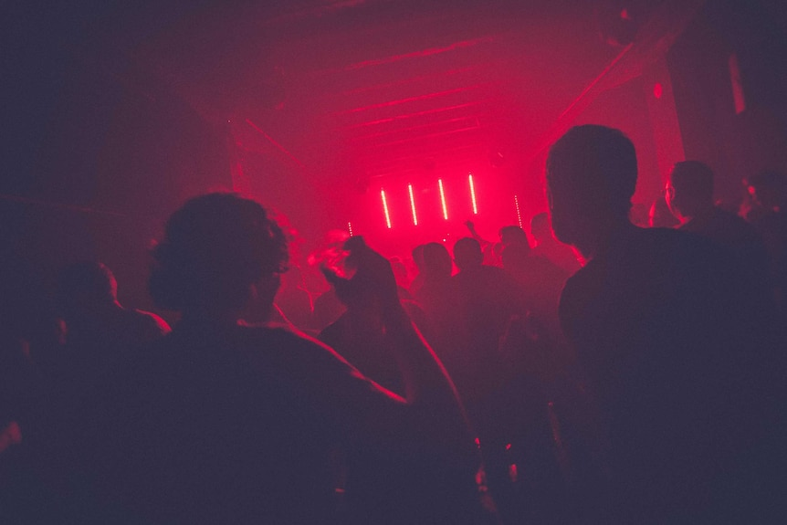 Silhouettes of people dancing in a nightclub bathed in red light.