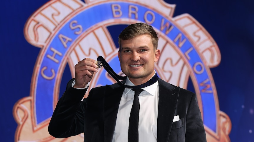 A Port Adelaide AFL player smiles at the camera and holds the Brownlow medal as it sits around his neck.