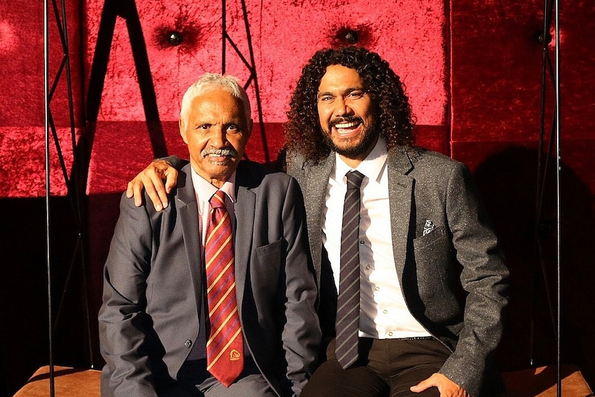 Nathan Appo smiling and posing with his father Neily Apps, both wear suits and sit on a bench.