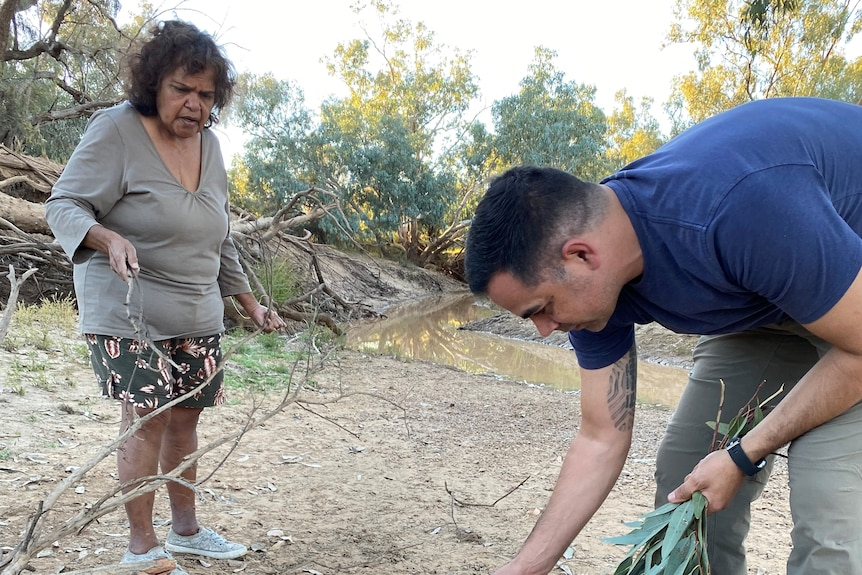 A young indigenous man lights a small fire with an Indigenous elder watching over him