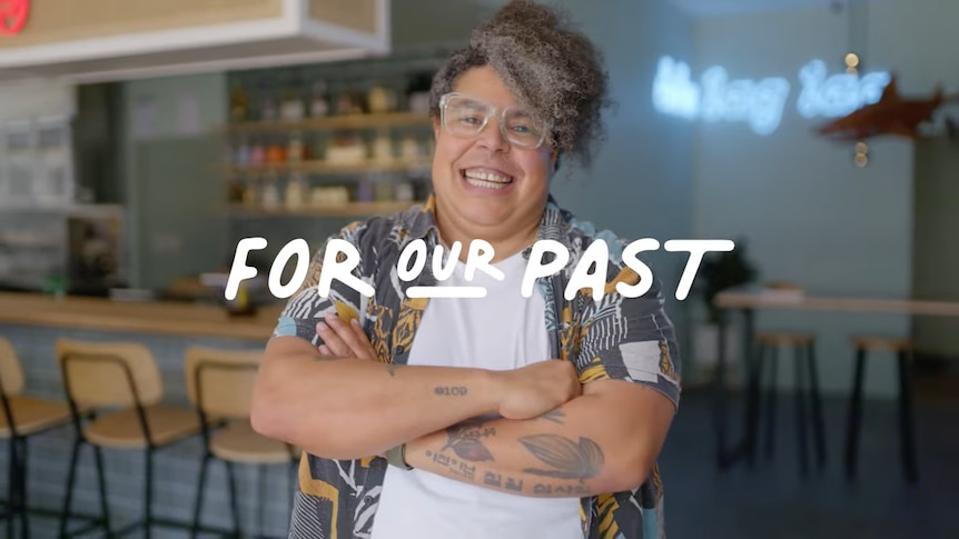 """An indigenous person wearing glasses smiles as they stand in front of a bar. The words """"For our past"""" are superimposed"""