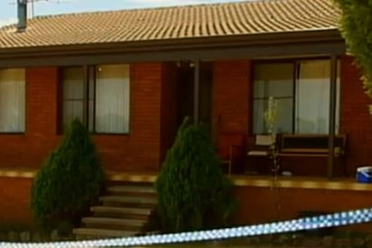 A grainy photo, apparently a television still, of a red brick house cordoned off with police tape.