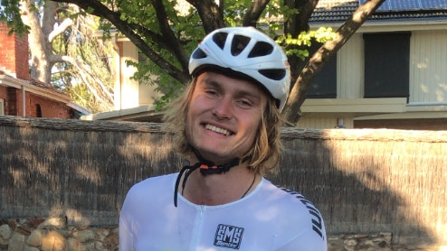 A young man with a big smile and wearing cycling gear stands with his bicyle