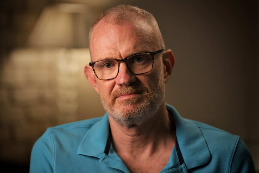 A man wears glasses and a blue collared shirt.