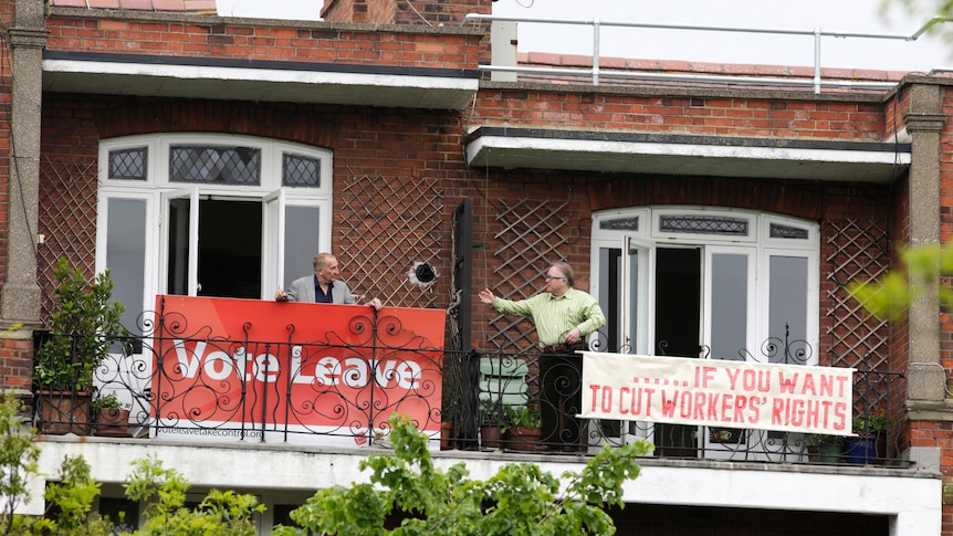 """Two London neighbours hold rival Brexit signs: left reads """"Vote Leave"""", right reads """"…if you want to cut workers rights"""""""