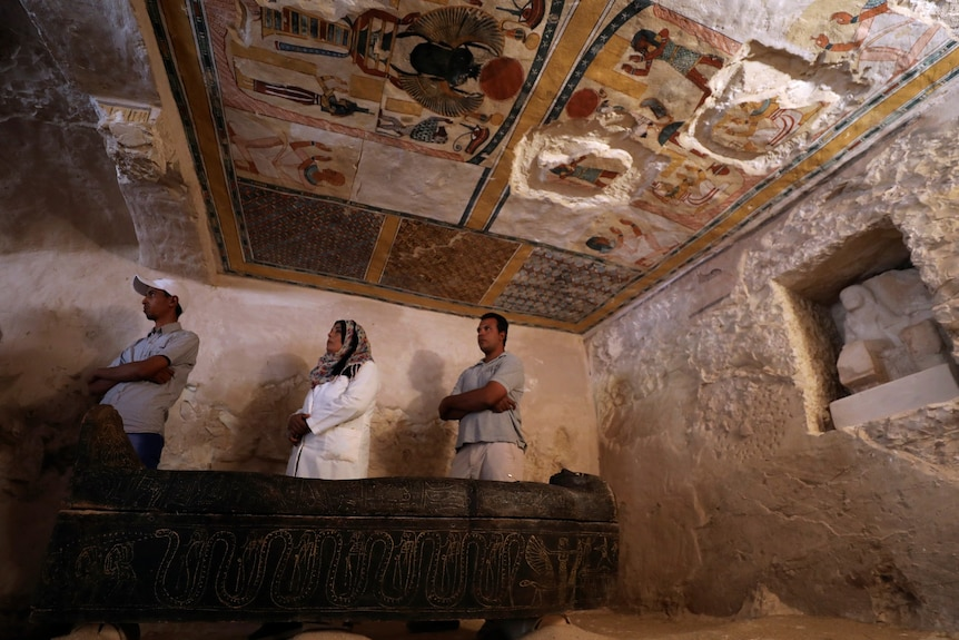 Two men and a woman wearing a headscarf stand in the tomb, beneath ad colourful painted ceiling showing Egyptian figures