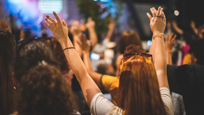 Members of a Christian congregation are shown from behind raising their arms.