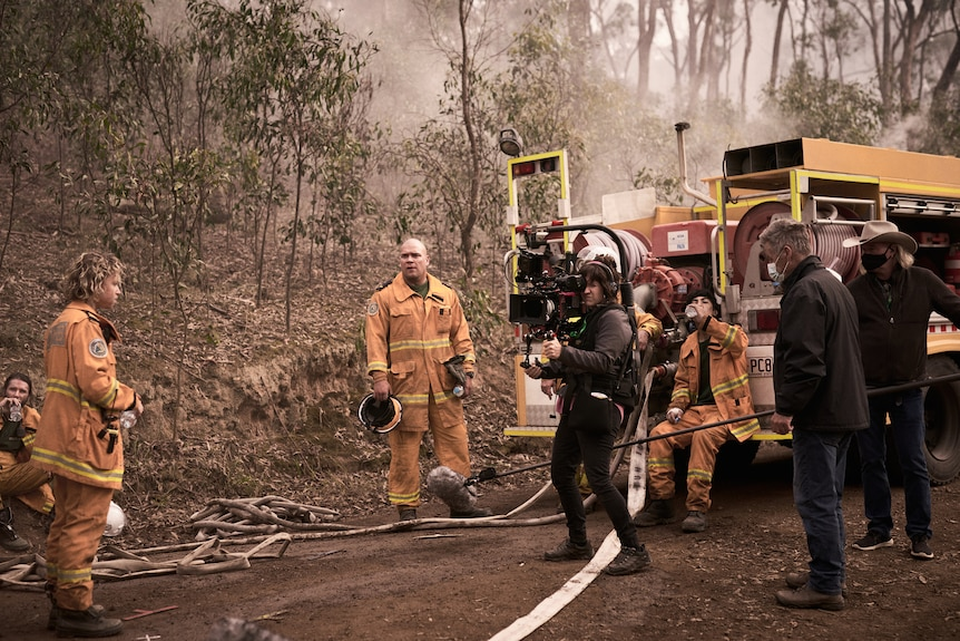 Actors wearing fire gear standing on road near fire truck while camera crew films.