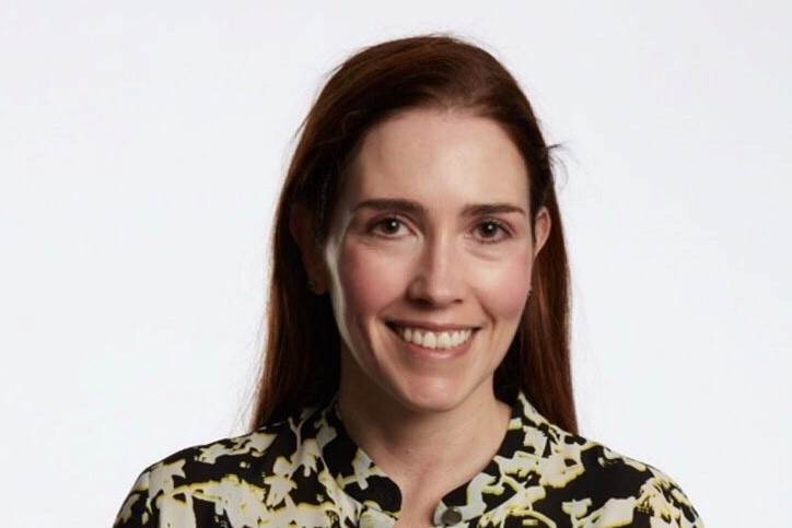 A woman smiles in front of a white background
