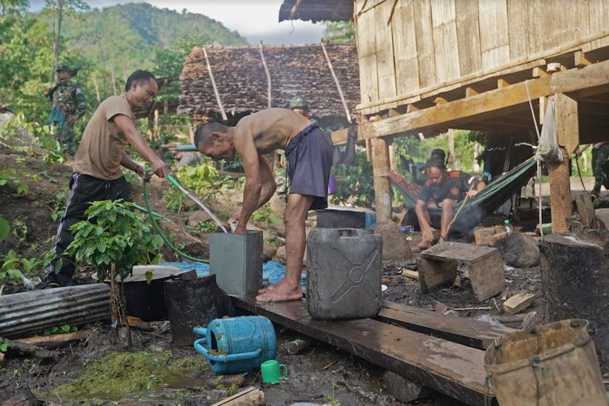 A man holds a hose while another washes his hands as others watch on near their house.