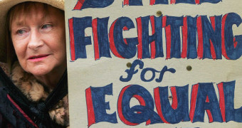 A woman holds a sign reading 'still fighting for equal pay'.