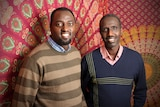 Claude Muco and Mutebutsi Bugegeri stand in front of a large piece of African fabric.
