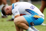 Gold Coast Titans player AJ Brimson squats on the ground after an NRL match.