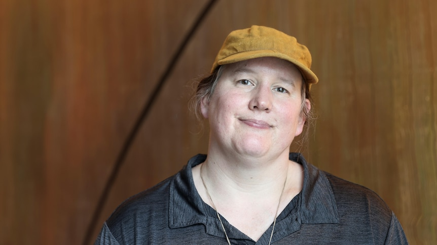 A woman wearing a cap looks at the camera