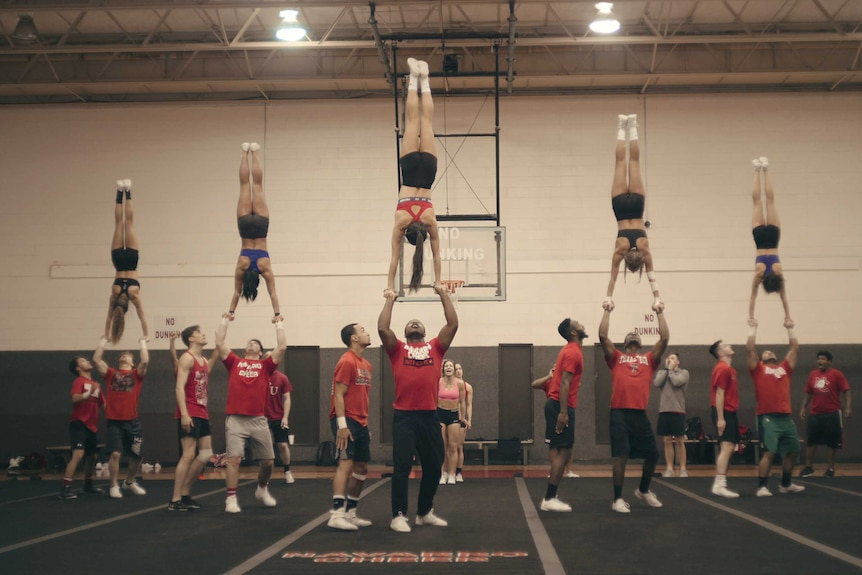 Five cheerleaders performing handstands balancing on other team members' hands, in story about cheerleading and Netflix Cheer.