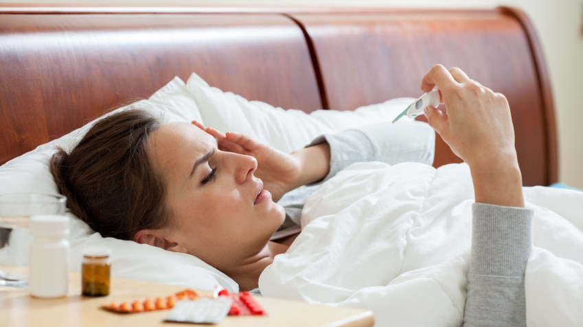 A woman lying in bed checking her temperature