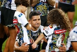 Cody Walker crouches down hugging his two children, standing up, with one in each arm