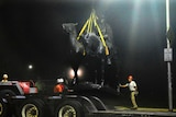 Workers load the monument onto a truck's trailer.