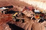 Trucks dig at a manganese mine