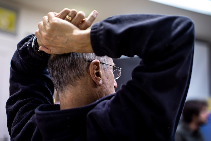 The back of Steve Marton, with both hands on his head, during the meeting.