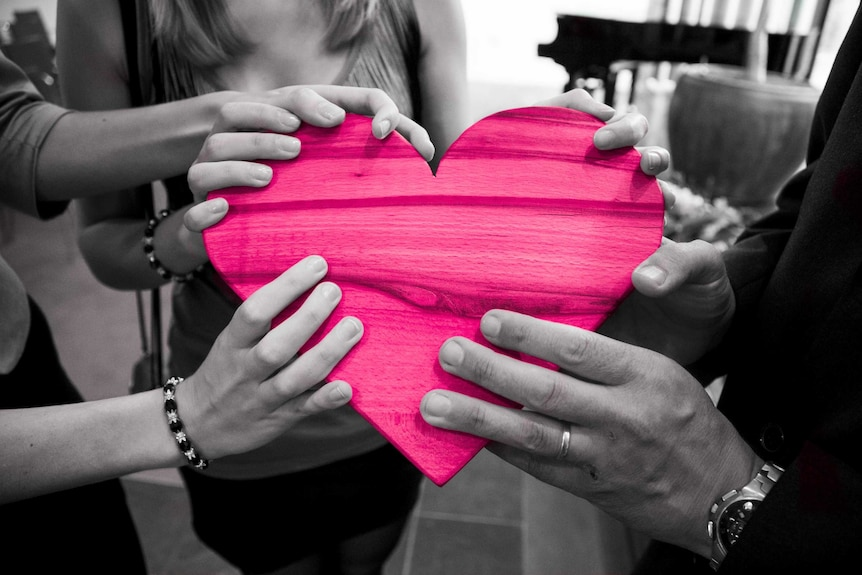 Monochrome hands holding a wooden heart with bright pink colouring