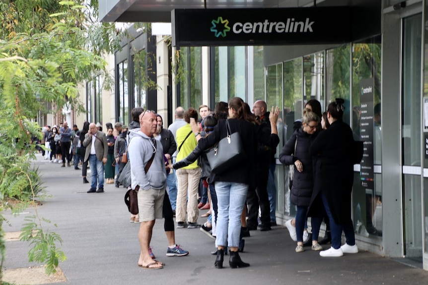 A queue of people stretches down York Street in South Melbourne, starting at the entrance to a Centrelink building.