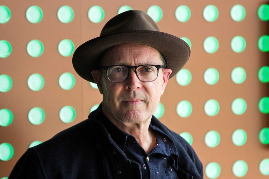 A man in a hat and glasses looks at the camera, green circular lights in background.