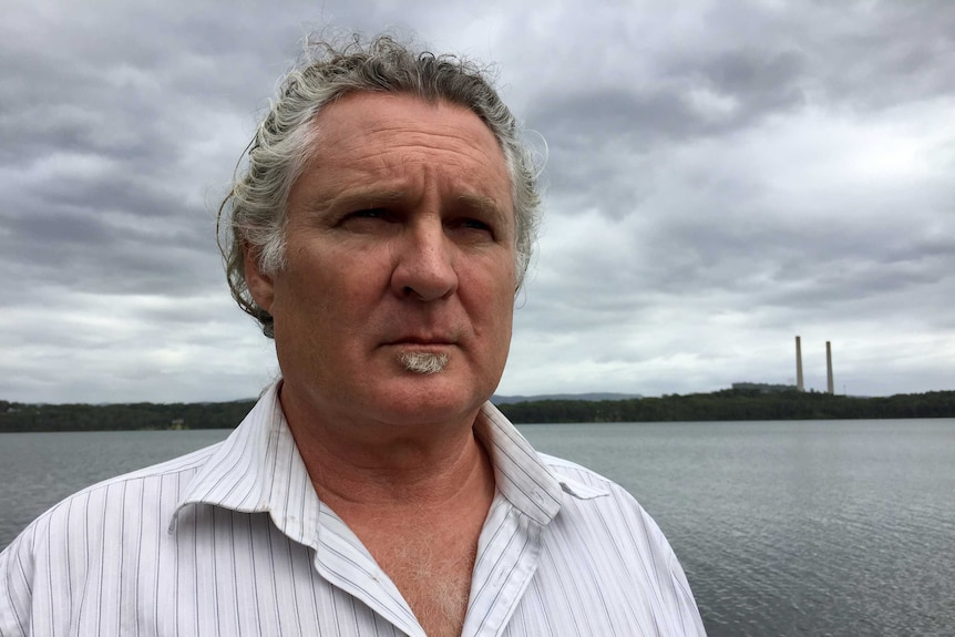 A headshot of a man looking out with Lake Macquarie in the background.
