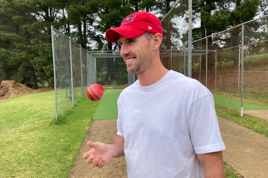 Shaun Tait throws a ball in the air in front of cricket nets.